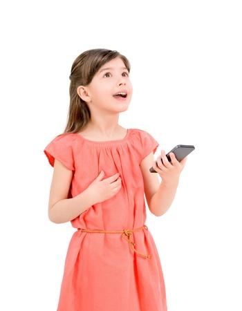 Ispirato piccolo ragazza in abito rosso guardando e tenendo in mano il suo telefono cellulare isolato su sfondo bianco photo