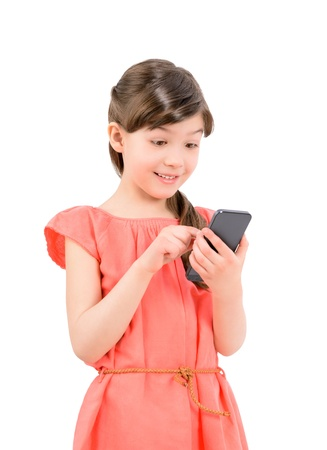 Wondering little cute girl in red dress surprised with an interesting information on mobile smartphone  Isolated on white background photo
