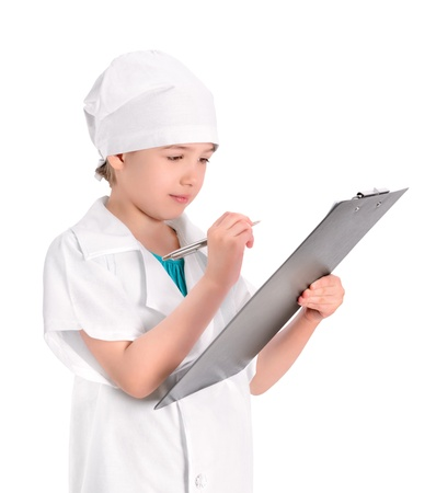 Serious little girl wearing as a nurse on white uniform writing prescription and preparing patients report  Isolated on white background  photo