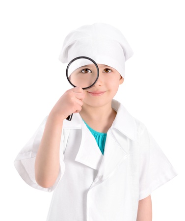 Portrait of a smiling little girl wearing as a nurse on white uniform and holding in right-hand a magnifying glass in front of her eye  Isolated on white background Stock Photo - 19382860