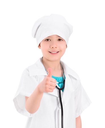 Portrait of a smiling little girl wearing as a doctor on white uniform, with a stethoscope, showing thumb up gesture photo