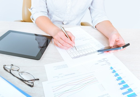 Successful businesswoman sitting at desk in casual clothes and using modern devices for  analyzing sales statistics for the month period of time Stock Photo - 19611302