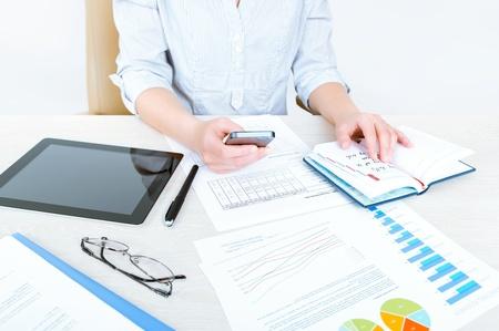 doelen: Succesvolle zakenvrouw zit aan bureau in casual kleding en planning haar werkdag op kantoor Stockfoto