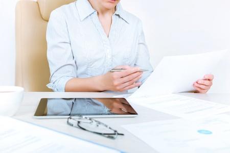 revisando documentos: Empresaria ocupada llevando en camisa ocasional que se sienta en el escritorio y comprobar los documentos en la oficina Foto de archivo