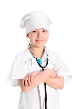 Portrait of a smiling little girl wearing as a nurse on white uniform, with a stethoscope, standing with her arms folded photo