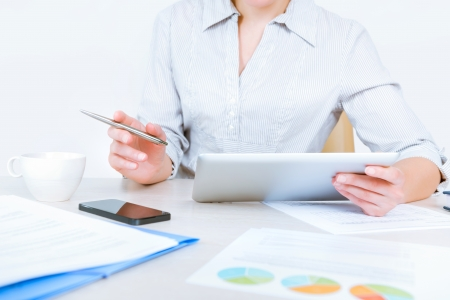 woman searching: Relaxed businesswoman wearing casual shirt sitting at desk and working with data on digital tablet in the office Stock Photo
