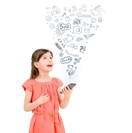 Happy cute little girl in red dress holding a smartphone  in hand and fascinated looking up at the icons of different entertainment apps  Isolated on white background