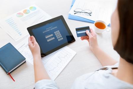 bank overschrijving: Succesvolle zakenvrouw zit aan bureau in casual kleding en het invoeren van haar wachtwoord en login aan online bankieren gebruik op digitale tablet in het kantoor uit te voeren Stockfoto