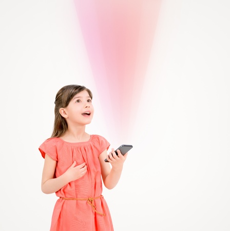 Inspired cute little girl in red dress looking up on ray of light from mobile phone in her hand  Isolated on beige background  photo
