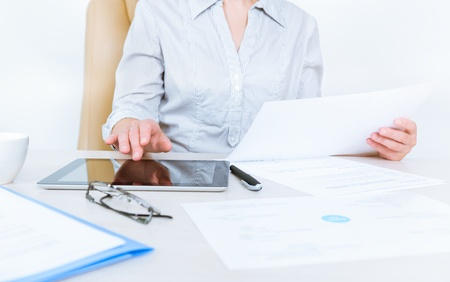 contabilidad: Persona de negocios llevaba en camisa ocasional que se sienta en el escritorio y comprobar los documentos con la ayuda de la tableta digital en la oficina