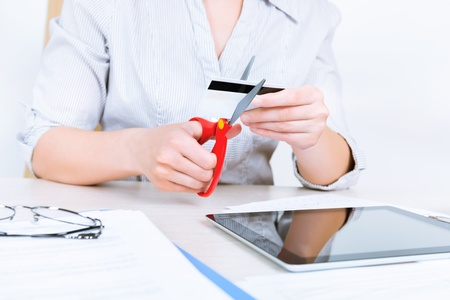 trouble free: Businesswoman sitting at desk in the office and getting rid of her credit card with the help of scissors after paying back a loan  Stock Photo