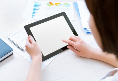 Caucasian businesswoman sitting at workplace and looking on blank modern digital tablet, touching on empty screen photo