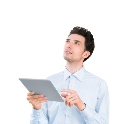 Portrait of a young handsome businessman holding tablet computer and looking up  Isolated on white background photo