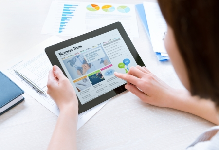 机に座ってとオフィスでデジタル タブレットに関する最新のビジネス ニュースを探していますカジュアルなシャツを着ている女性実業家 写真素材