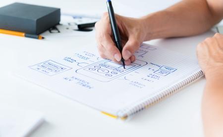 디자이너는 모바일 애플리케이션의 가용성을 개발하고 종이에 자사의 프레임 워크를 그리기 스톡 콘텐츠