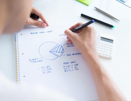 ganancias: Persona que se sienta en el escritorio, el c�lculo de los ingresos de las ventas y el dibujo diagrama circular con n�meros