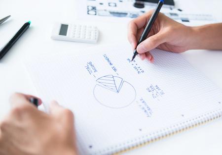 계획: 사람, 책상에 앉아 가정의 소득을 계산하고 숫자 원형 다이어그램을 그리기