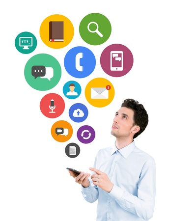 Handsome young man holding smartphone and looking on collection of colorful mobile application icons on communication and mobile connection theme  Isolated on white background  Banco de Imagens