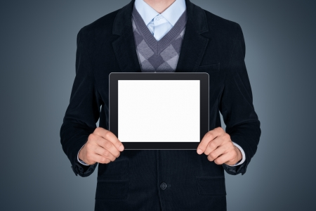 Handsome businessman in black suit showing modern digital tablet with blank screen  Studio shot  Isolated on dark gray background photo