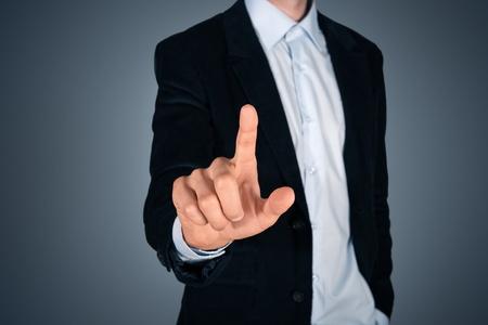 �cran tactile: Portrait d'homme d'affaires pensive toucher une image vide invisible de l'�cran tactile de l'�cran concept Isol� sur fond gris fonc�