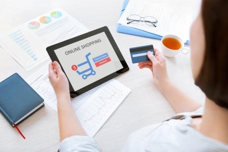 Joven empresaria caucásica sentado en el escritorio de la oficina y el uso de tarjetas de crédito y la tableta digital moderna para hacer compras en línea