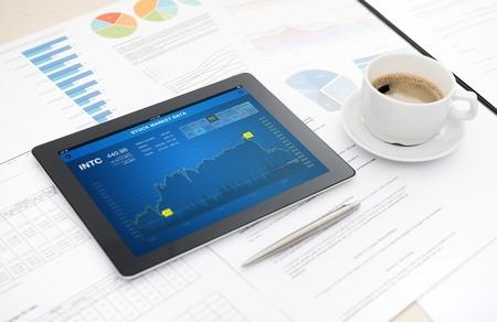 analytic: Tableta digital moderna con la acci�n de aplicaci�n de datos de mercado en la pantalla en un escritorio con algunos papeles y documentos, bol�grafo y una taza de caf� Foto de archivo