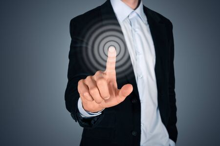 Portrait of business person touching button on invisible screen  Touch screen concept image  Isolated on dark gray background Stock Photo - 21090448