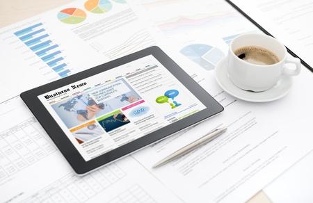 いくつかペーパーおよび文書、ペン、一杯のコーヒーと机の上に横たわって画面上のビジネス メディアのウェブサイトと現代のデジタル タブレット