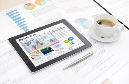 Moderne digitale tablet met zakelijke media website op een scherm liggend op een bureau met een aantal papieren en documenten, pen en kopje koffie
