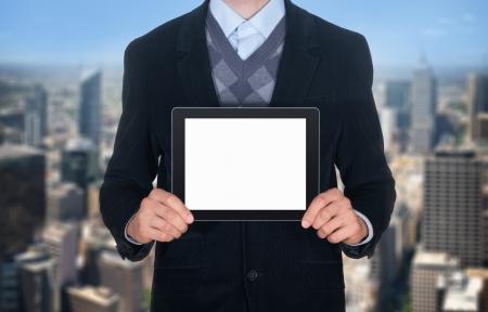 ビジネス: 画面が空白に分離された都市景観背景と黒のスーツ示す現代デジタル タブレットでハンサムなビジネスマン