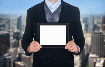 Handsome businessman in black suit showing modern digital tablet with blank screen  Isolated on cityscape background  photo