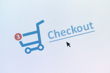 e commerce icon: Closeup photo of shopping cart with items and checkout link on the monitor screen