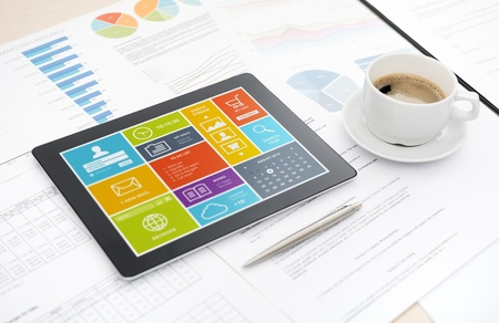 いくつかペーパーおよび文書、ペン、一杯のコーヒーと机の上に横たわって画面上のカラフルな近代的なユーザー インターフェイスと現代のデジタ 写真素材