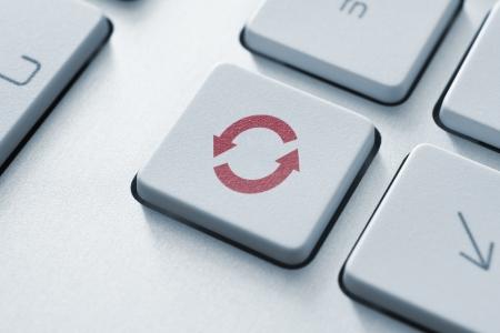 Botón con el icono de actualizar o syncrhonize en un teclado de computadora moderna