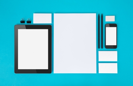 Set of variety blank office objects organized for company presentation or branding identity with blank modern devices  Isolated on blue paper background  photo