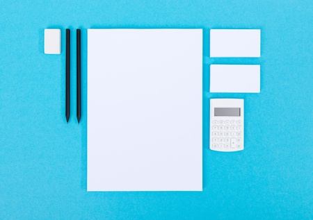 Set of variety blank office objects organized for company presentation or branding identity  Isolated on blue paper background Stock Photo - 22076798