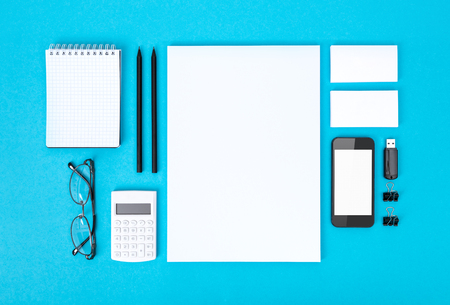 composition notebook: Set of variety blank office objects organized for company presentation or corporate identity  Isolated on blue paper background  Stock Photo