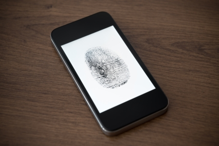 fingerprint: Modern mobile phone with fingerprint mark on a screen lying on brown wooden desk  Mobile security concept Stock Photo