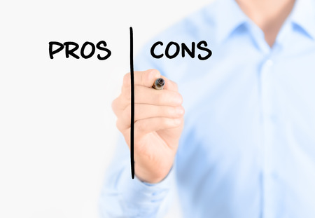 comparison: Young businessman holding  a marker and writing pros and cons comparison concept for weigh all arguments  Isolated on white background  Stock Photo