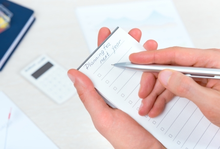 Business person thinking and writing new planning to-do list in schedule checklist book for the next year with ballpoint pen in the office Stock Photo - 24027952