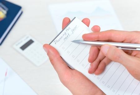 persona pensando: Persona de negocios pensando y escribiendo la nueva planificaci�n de tareas en la lista de libros checklist calendario para el a�o que viene con el bol�grafo en la oficina
