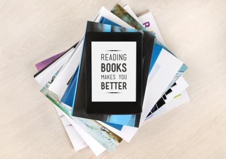 apilar: La lectura de libros te hace mejor - texto en una pantalla de libro electrónico que se encuentra en la cima de una pila de libros y revistas el concepto de aprendizaje de nuevos conocimientos y el desarrollo de las capacidades mentales
