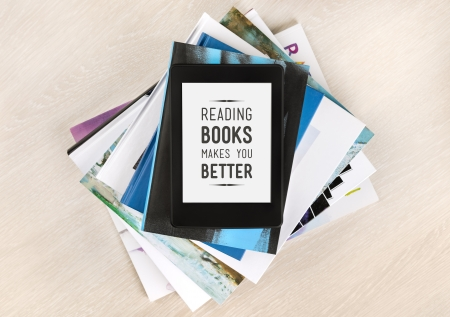 Reading books makes you better - text on a screen of electronic book which lies on top of a pile of books and magazines  Concept of learning new knowledge and the development of mental abilities  Stok Fotoğraf