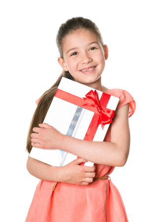 KIEV, UKRAINE - MAY 26, 2014: Smiling little girl holding in hands brand new Apple iPad Air as birthday present. Apple iPad Air developed by Apple inc. and was released on November 1, 2013.