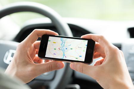 gps navigation: KIEV, Ucrania - 16 de mayo 2014: El hombre en el coche planificar una ruta mediante una aplicaci�n de Google Maps en el iPhone de Apple 5S. Google Maps es un servicio de mapas web m�s popular para m�vil proporcionada por Google inc. Editorial