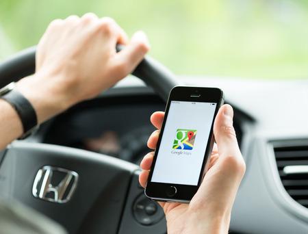 elhelyezkedés: Kiev, Ukrajna - május 16, 2014: Az ember az autóban tervez útvonalat a Google Maps alkalmazás Apple iPhone 5S. A Google Maps a legnépszerűbb internetes térképészeti szolgáltatás a mobil a Google által biztosított inc.