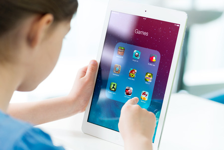niños jugando: KIEV, Ucrania - 21 de mayo 2014: Niña que mira en un nuevo iPad de Apple de aire con varias aplicaciones de juegos en una pantalla. Apple iPad Aire desarrollado por Apple inc. y fue lanzado el 1 de noviembre de 2013. Editorial