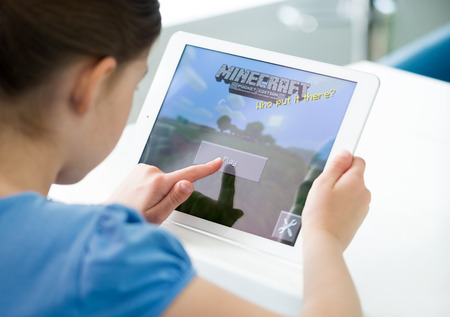 KIEV, UKRAINE - MAY 21, 2014: Little girl start playing Minecraft game on brand new Apple iPad Air. Minecraft is very popular game for mobile devices, was released for iOS version on November 17, 2011