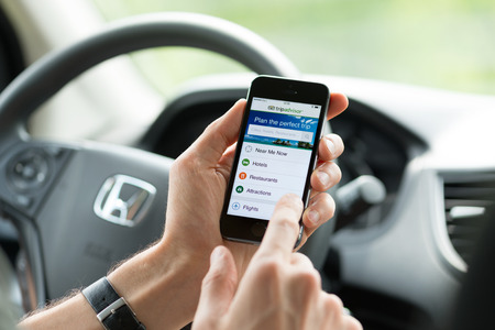 KIEV, UKRAINE - MAY 16, 2014: Man in a car planning a trip using Tripadvisor app on Apple iPhone 5S. Tripadvisor is a travel guide source providing reviews, photos and advice for hotels and vacations.