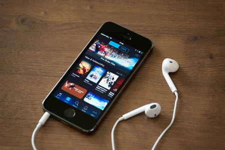 KIEV, UKRAINE - JUNE 05, 2014: Brand new Apple iPhone 5S with iTunes store application on the screen lying on a desk with headphones. iTunes is the media library with player for download and organize media files, developed by Apple Inc.